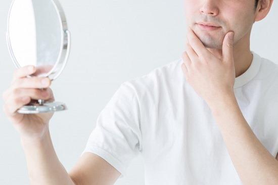鏡を見る男性の画像